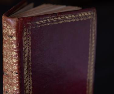 Detail of a printed book shows red binding with gold details at the borders of the boards and all along the spine.