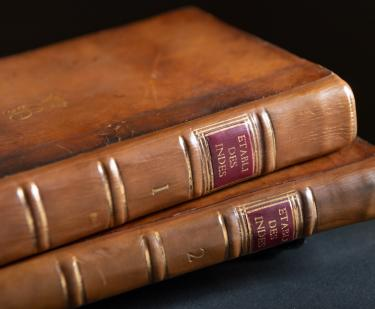 "Detail of two books shows brown leather binding and spine labels ""1"" and ""2"" and the shortened title."