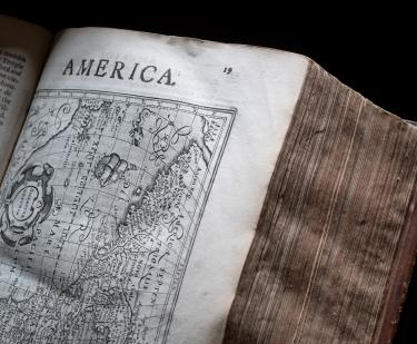 "Detail of a printed book shows a full-page map and text at the of the page reading ""America."""