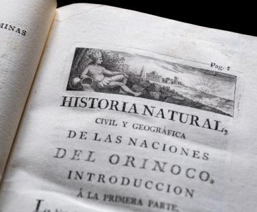 Detail of a printed book shows a decorative head piece on the title page written in Spanish.