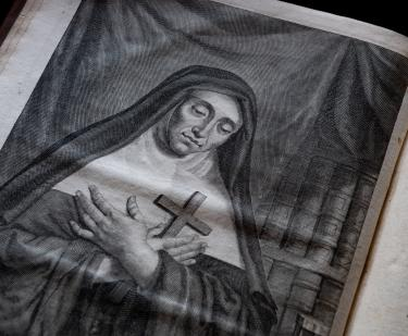 Detail of a printed book shows an illustration of a nun holding a cross to her chest.