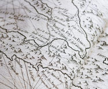 Detail of a printed map shows text in French, latitude and longitude lines, and small mountains.