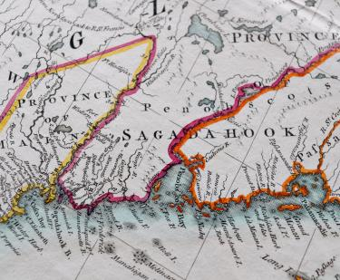 "Detail of a colored, engraved map shows pink, orange, and yellow used to outline areas and labels in English such as ""Penobscots."""