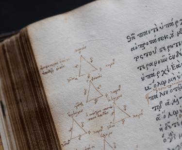 Detail of a printed text in Greek and manuscript notations of triangles and Greek text written in the margins.