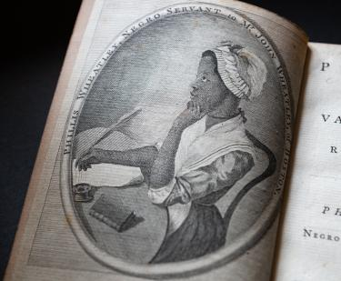 Detail of a printed book shows a portrait frontispiece of Phillis Wheatley sitting at a table with a quill in her hand in the process of writing.