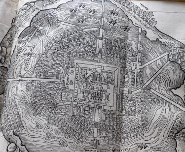 Detail of a fold-out printed map shows town square in the center, surrounding buildings, and ships at sea at the outer perimeter.