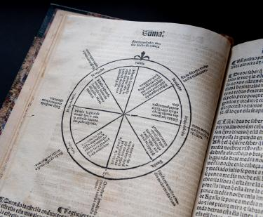 Detail of a printed book shows a circular illustration and text in Spanish.