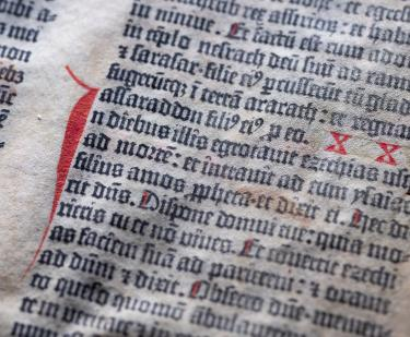 Detail of a leaf of the Gutenberg bible printed in black and red ink shows Latin text.