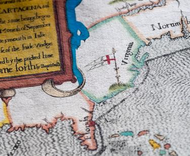 "Detail of a colored, engraved map shows ""Florida,"" ""Virginia,"" and partial view of frontispiece with text in English."