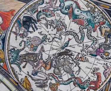 "Detail from an engraved, hand colored map shows vivid illustrations of celestial sphere with their constellations and zodiac signs around the sun. Labels in Dutch read ""Taurus,"" ""Orion,"" and ""Saittarius."""