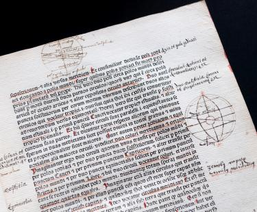 Detail from a printed book shows red and black text in Latin, geometrical sketches in the margins, and manuscript notations in the margins and underlining.