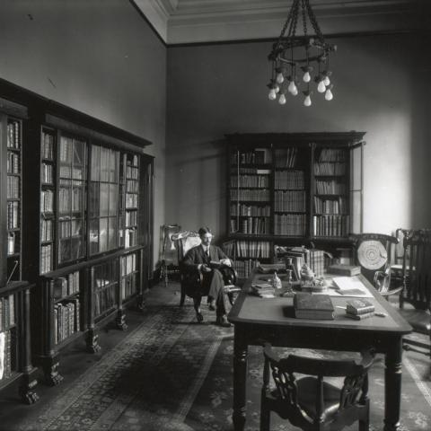 George Parker Winship in Library surrounded by books