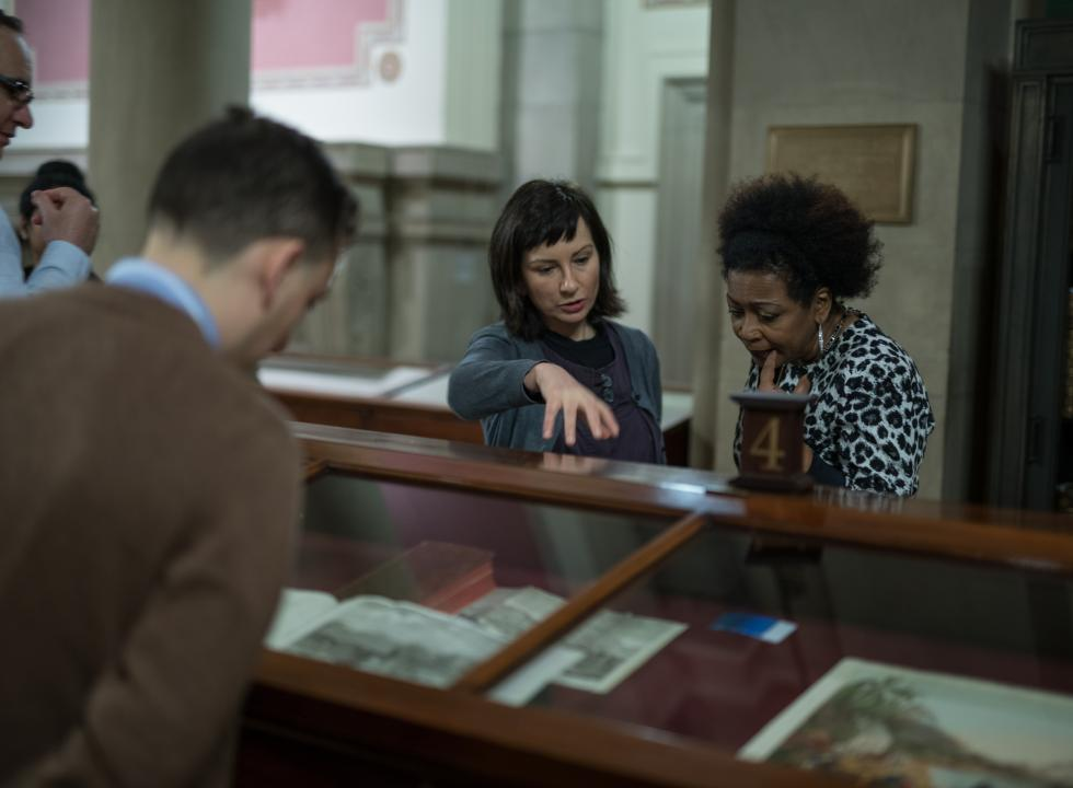 Library curator discusses materials in an exhibition with a visitor