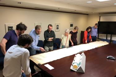 group of people standing around a map measuring over 14 feet long