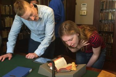 two people standing over a table looking at a rare book